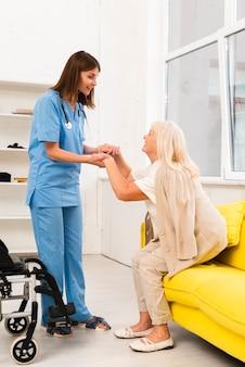 Badante che aiuta donna anziana che si alza