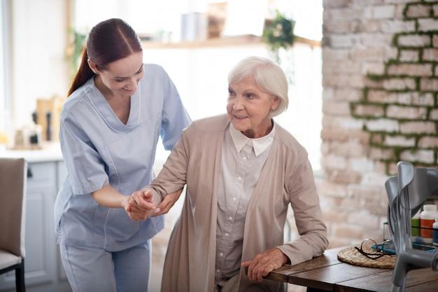 Badante che sorride mentre aiutando donna invecchiata a camminare