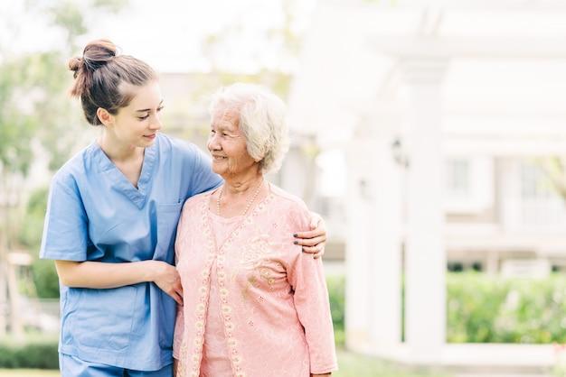 Badante con donna anziana asiatica all'aperto