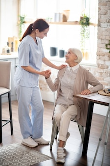 Badante dai capelli rossi in uniforme parlando con il paziente