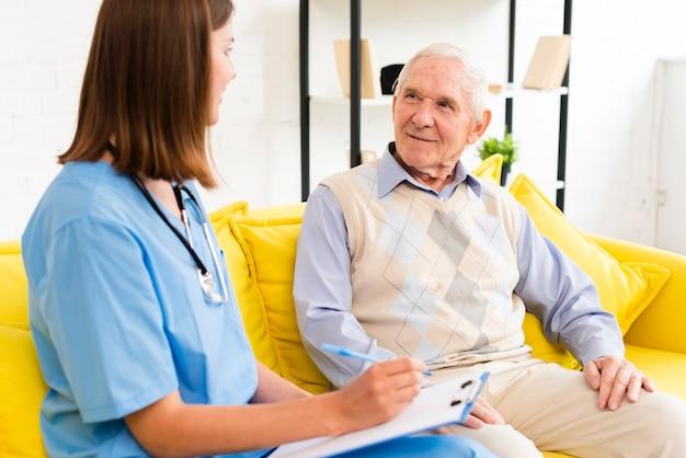 Badante di colpo medio che parla con uomo anziano