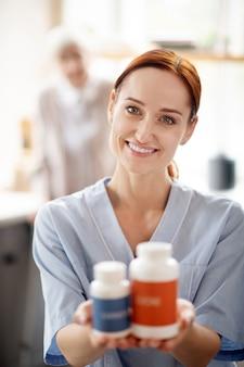 Badante in possesso di vitamine e integratori per il paziente