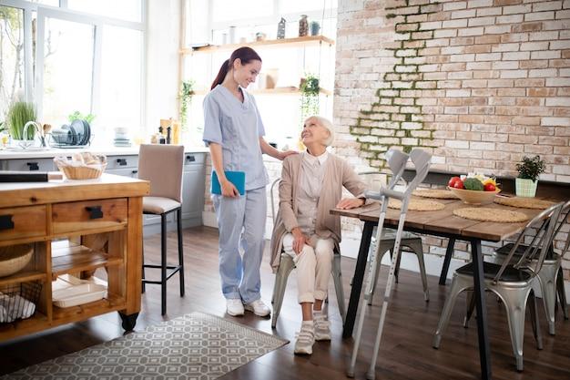 Badante in uniforme che viene a visitare una donna anziana