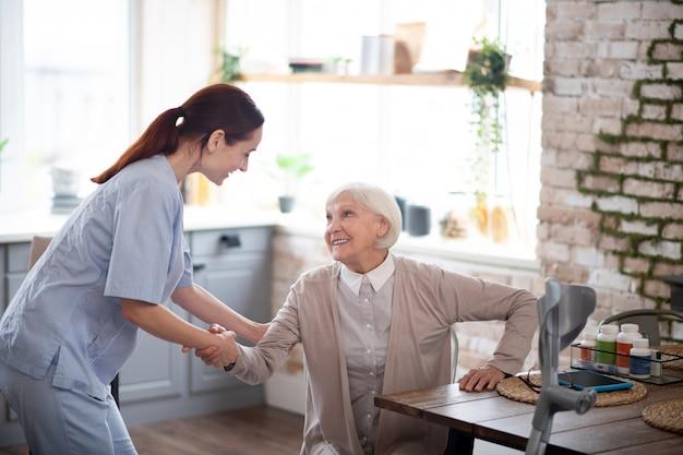 Badante piacevole che aiuta donna invecchiata a alzarsi