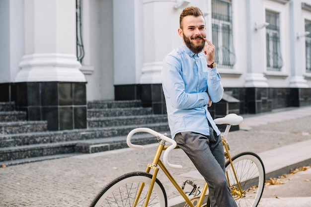 Baffi commoventi sorridenti dell'uomo vicino alla bicicletta