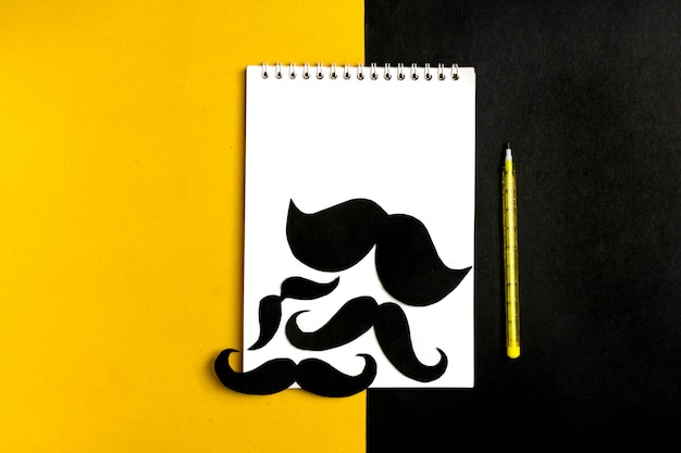 Baffi di carta nera, blocco note, penna, sfondo giallo
