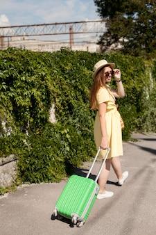 Bagagli di trasporto della donna della foto a figura intera