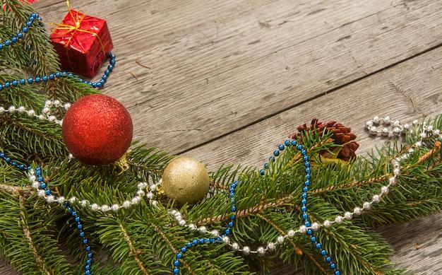 Bagattelle della decorazione di natale con i rami dell'albero di abete su fondo di legno