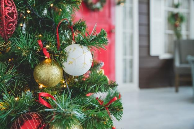 Bagattelle di natale con il nastro riccio sull'albero di abete. castello di bello albero di natale con i giocattoli dorati, bianchi, rossi. decorazioni di capodanno. sfondo scintillante e fata. buon natale e felice anno nuovo