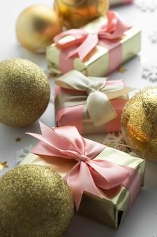 Bagattelle gloden dei bei regali dorati su bianco. natale, festa, compleanno sfondo. festeggia il copyspace shinny delle scatole a sorpresa. vista dall'alto piatto creativo.