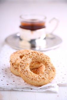 Bagel con semi di sesamo e una tazza di tè su uno sfondo bianco