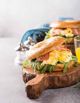 Bagel con uova strapazzate, rucola e pancetta fritta