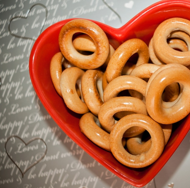 Bagel sul piatto rosso a forma di cuore su grigio.