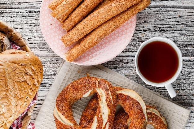 Bagel turco con una tazza di tè e pane su superficie di legno, vista superiore.