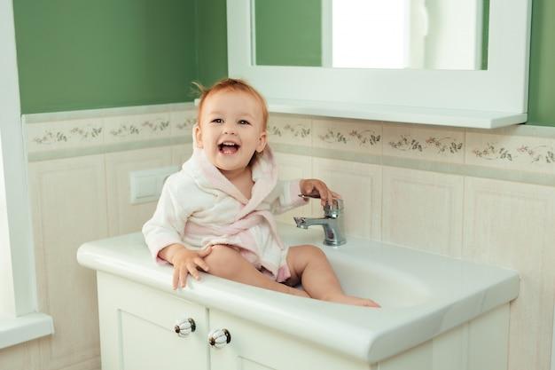 Bagnetto e igiene del bambino. prendersi cura dei bambini piccoli. ragazza carina affascinante 1 anno di età in un accappatoio bianco si siede nel lavandino in bagno