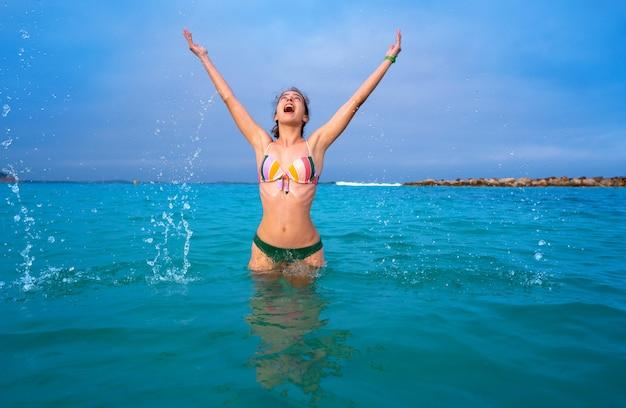 Bagno della ragazza della giovane donna nella spiaggia di ibiza