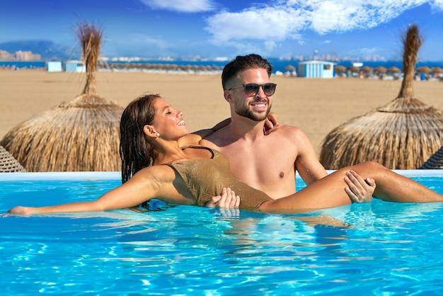 Bagno di coppia turistica in piscina a sfioro su una spiaggia