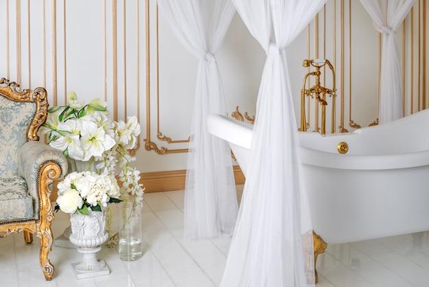 Bagno di lusso in colori chiari con dettagli di mobili dorati e baldacchino. interni classici eleganti.
