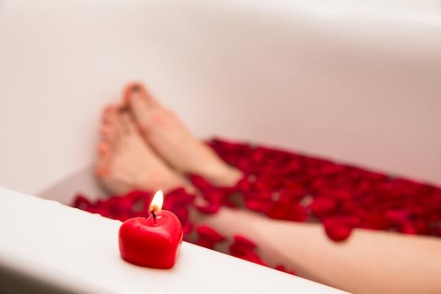 Bagno romantico di san valentino, centro benessere, bagno con petali di rosa, candela cuore rosso