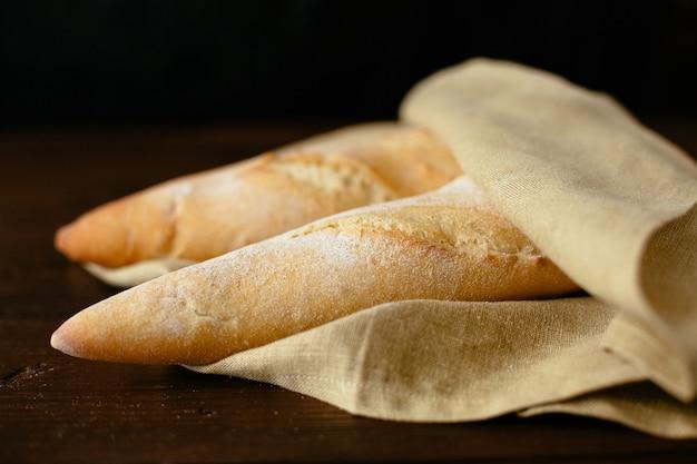 Baguette appena sfornata. due baguette appena sfornate avvolte in una panetteria.