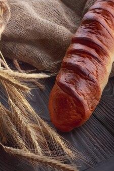 Baguette e grano sulla tavola di legno