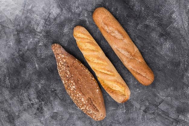 Baguette e pagnotta su sfondo stagionato