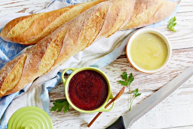 Baguette francesi croccanti fresche con patè di fegato di pollo e marmellata di bacche su uno sfondo bianco invecchiato. patè di pollo casalingo fresco su pane