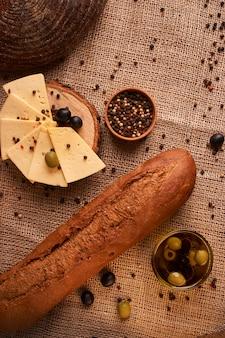 Baguette italiane fresche sulla tavola di legno con olio fuoco selettivo e molle