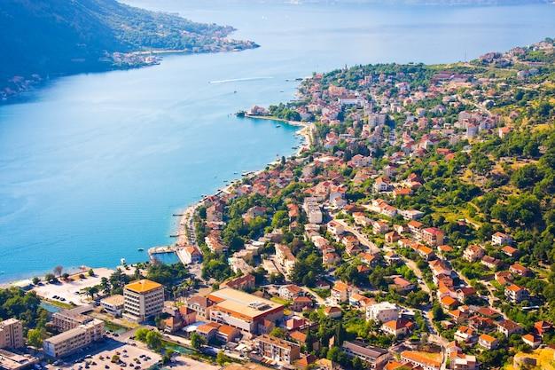 Baia di cattaro in montenegro con vista sulle montagne, barche e vecchie case con tetti di tegole rosse