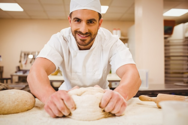 Baker impastare la pasta a un bancone in una cucina commerciale