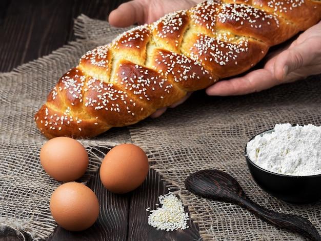 Baker mette il pane intrecciato di pasqua sul tavolo