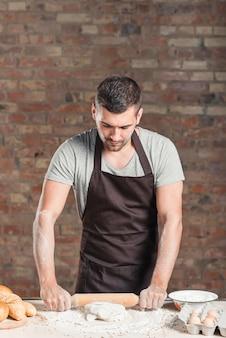 Baker premendo impasto con mattarello sul bancone della cucina