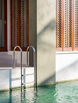 Balcone esterno a bordo piscina con scala e sedia