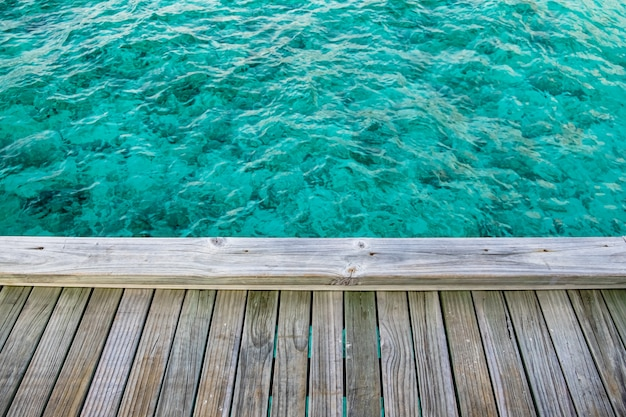 Balcone in legno sul magnifico mare cristallino delle maldive