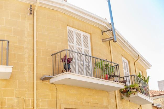 Balconi con fiori in una bella casa in pietra. avvicinamento. vista dal basso