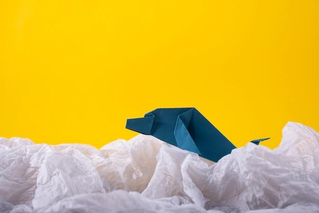 Balena su un'arte artigianale di carta artigianale origami onda su uno sfondo di carta gialla