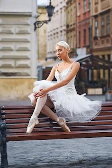 Ballerina attraente che si siede in panchina in città