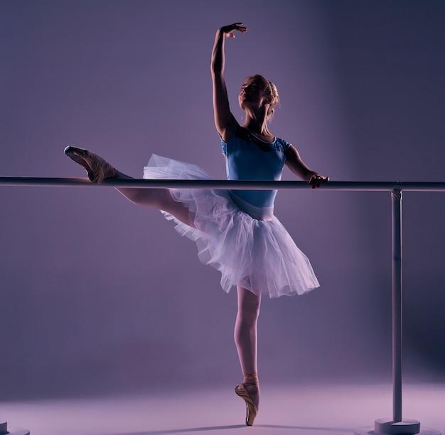Ballerina classica che propone alla sbarra di balletto