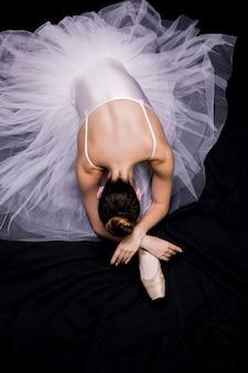 Ballerina di alto angolo che si siede sulla sua gamba
