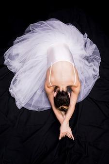 Ballerina di disposizione piana che si siede sul backround nero