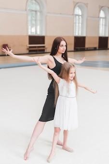 Ballerina e ragazza che praticano in studio di danza