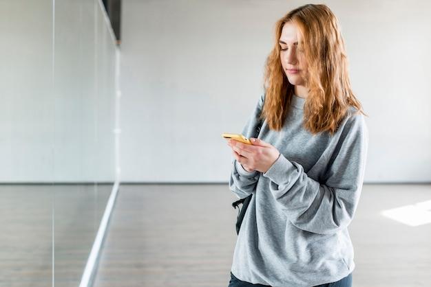 Ballerina femminile utilizzando il telefono cellulare