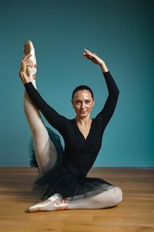 Ballerina graziosa della donna in tutu e pointe in costume da bagno nero che posa nello studio su fondo blu