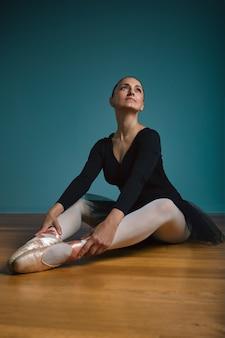Ballerina graziosa della donna in tutu e pointe in costume da bagno nero che posa nello studio sulla parete blu