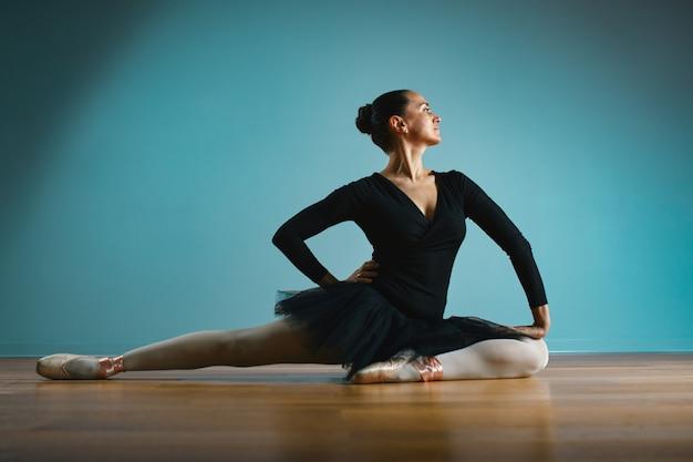Ballerina graziosa della donna in tutu e pointe in costume da bagno nero che posa nello studio