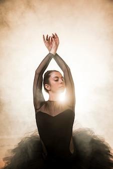 Ballerina graziosa di vista frontale nel fumo