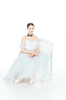 Ballerina in abito bianco seduto, spazio di studio.