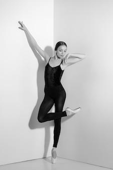 Ballerina in abito nero in posa su scarpe da punta