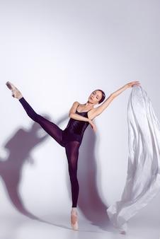 Ballerina in attrezzatura nera che posa sulle dita del piede, fondo dello studio.