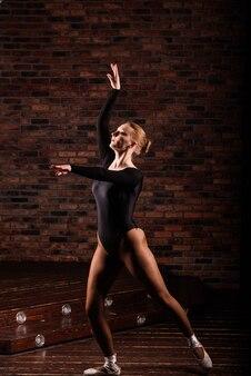 Ballerina in tuta scura, in abito scuro interno studio.